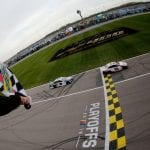 KANSAS CITY, KANSAS - OCTOBER 20: Denny Hamlin, driver of the #11 FedEx Office Toyota, takes the checkered flag ahead of Chase Elliott, driver of the #9 NAPA Auto Parts Chevrolet,  to win the Monster Energy NASCAR Cup Series Hollywood Casino 400 at Kansas Speedway on October 20, 2019 in Kansas City, Kansas. (Photo by Jonathan Ferrey/Getty Images)   Getty Images