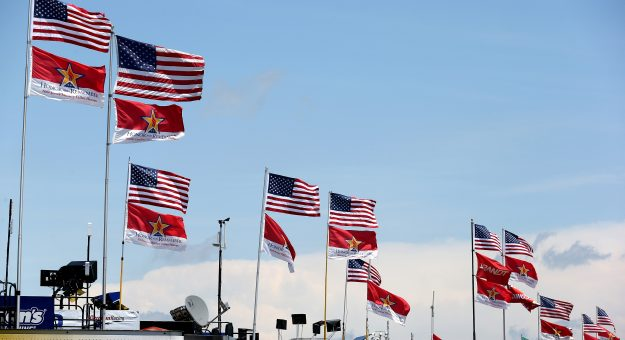 CHARLOTTE, NC - MAY 21:  Flags fly on top of haulers in the garage area during practice for the NASCAR Sprint Cup Series Coca-Cola 600 at Charlotte Motor Speedway on May 21, 2015 in Charlotte, North Carolina.  (Photo by Streeter Lecka/Getty Images) | Getty Images