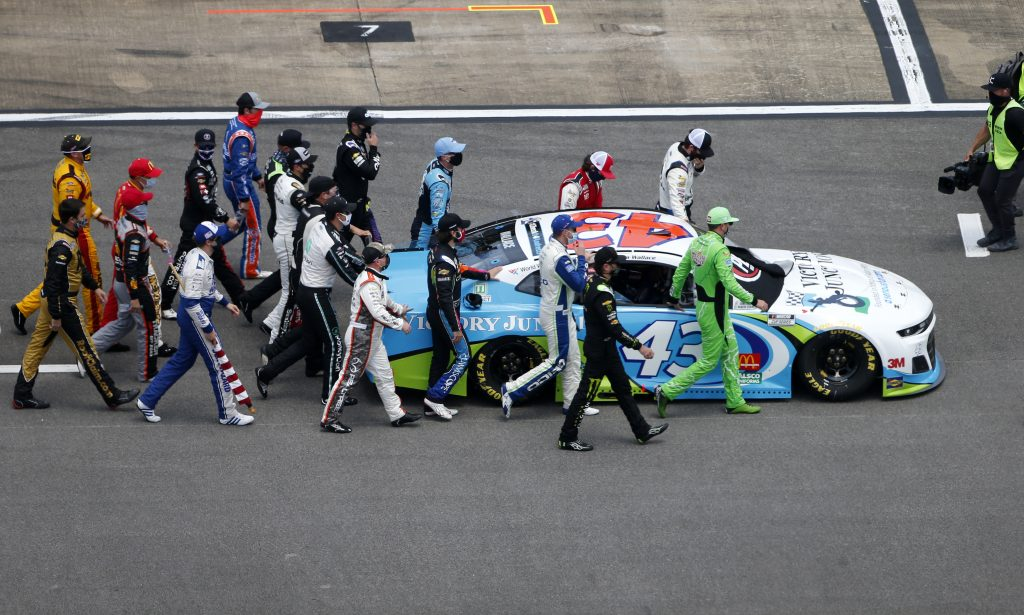 TALLADEGA, ALABAMA - JUNE 22: NASCAR drivers push the #43 Victory Junction Chevrolet, driven by Bubba Wallace, to the front of the grid as a sign of solidarity with the driver prior to the NASCAR Cup Series GEICO 500 at Talladega Superspeedway on June 22, 2020 in Talladega, Alabama. A noose was found in the garage stall of NASCAR driver Bubba Wallace at Talladega Superspeedway a week after the organization banned the Confederate flag at its facilities. (Photo by Brian Lawdermilk/Getty Images) | Getty Images