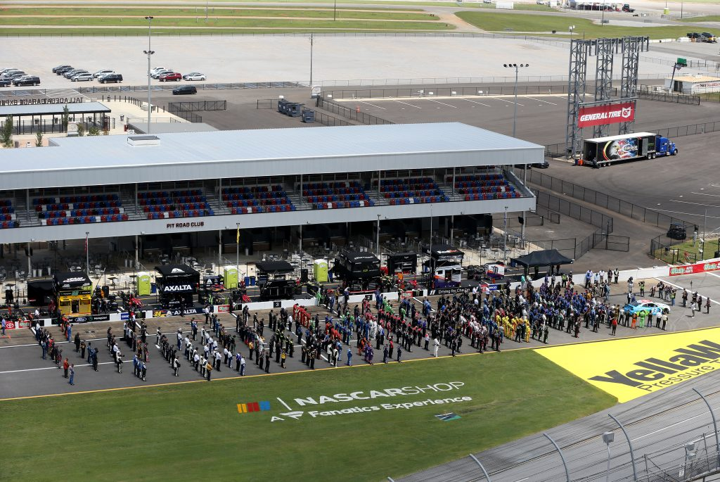 TALLADEGA, ALABAMA - JUNE 22: NASCAR drivers stand in solidarity with Bubba Wallace, driver of the #43 Victory Junction Chevrolet, during pre-race ceremonies prior to the NASCAR Cup Series GEICO 500 at Talladega Superspeedway on June 22, 2020 in Talladega, Alabama. A noose was found in the garage stall of NASCAR driver Bubba Wallace at Talladega Superspeedway a week after the organization banned the Confederate flag at its facilities. (Photo by Brian Lawdermilk/Getty Images) | Getty Images
