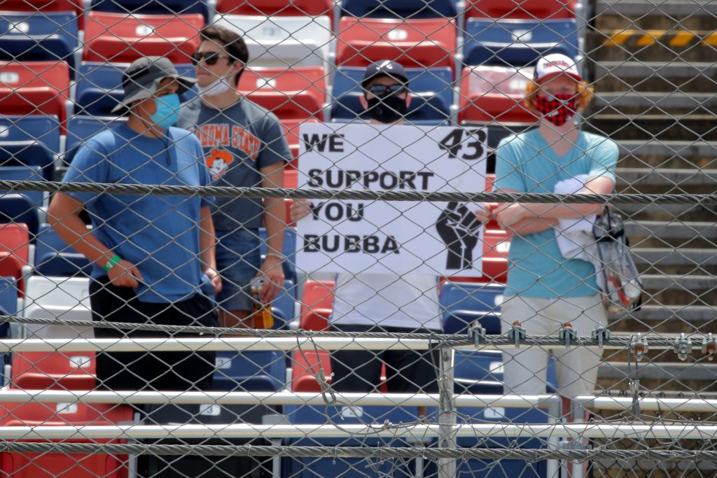TALLADEGA, ALABAMA - JUNE 22: Fans hold a sign in support of Bubba Wallace, driver of the #43 Victory Junction Chevrolet, prior to the NASCAR Cup Series GEICO 500 at Talladega Superspeedway on June 22, 2020 in Talladega, Alabama. A noose was found in the garage stall of NASCAR driver Bubba Wallace at Talladega Superspeedway a week after the organization banned the Confederate flag at its facilities. (Photo by Chris Graythen/Getty Images) | Getty Images