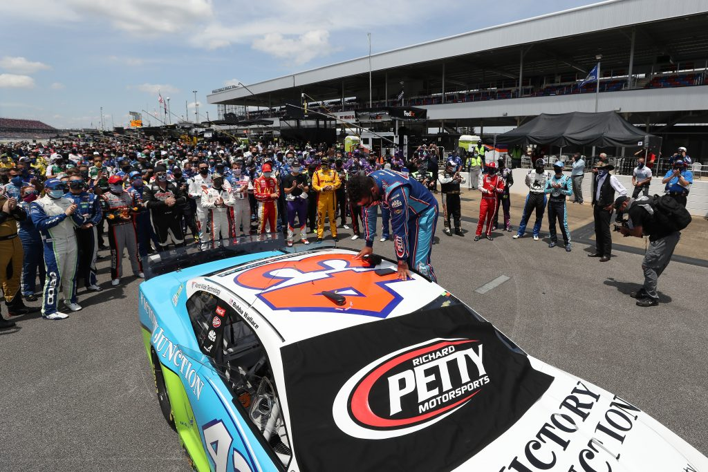 TALLADEGA, ALABAMA - JUNE 22: NASCAR drivers stand in solidarity with Bubba Wallace, driver of the #43 Victory Junction Chevrolet, during pre-race ceremonies prior to the NASCAR Cup Series GEICO 500 at Talladega Superspeedway on June 22, 2020 in Talladega, Alabama. A noose was found in the garage stall of NASCAR driver Bubba Wallace at Talladega Superspeedway a week after the organization banned the Confederate flag at its facilities. (Photo by Chris Graythen/Getty Images) | Getty Images