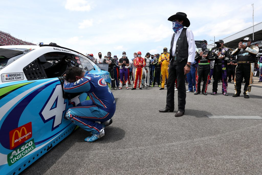 TALLADEGA, ALABAMA - JUNE 22: Bubba Wallace, driver of the #43 Victory Junction Chevrolet, kneels as team owner, and NASCAR Hall of Famer Richard Petty and NASCAR drivers stand in solidarity with Wallace prior to the NASCAR Cup Series GEICO 500 at Talladega Superspeedway on June 22, 2020 in Talladega, Alabama. A noose was found in the garage stall of NASCAR driver Bubba Wallace at Talladega Superspeedway a week after the organization banned the Confederate flag at its facilities. (Photo by Chris Graythen/Getty Images) | Getty Images