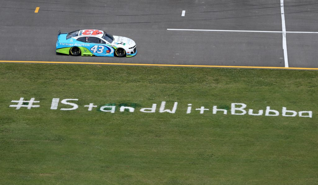 TALLADEGA, ALABAMA - JUNE 22: Bubba Wallace, driver of the #43 Victory Junction Chevrolet, drives past the #IStandWithBubba stencil on the field prior to the NASCAR Cup Series GEICO 500 at Talladega Superspeedway on June 22, 2020 in Talladega, Alabama. A noose was found in the garage stall of NASCAR driver Bubba Wallace at Talladega Superspeedway a week after the organization banned the Confederate flag at its facilities. (Photo by Brian Lawdermilk/Getty Images) | Getty Images