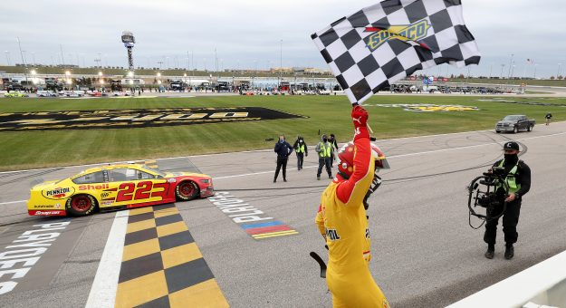 KANSAS CITY, KANSAS - OCTOBER 18: Joey Logano, driver of the #22 Shell Pennzoil Ford, celebrates with the checkered flag after winning the NASCAR Cup Series  Hollywood Casino 400 at Kansas Speedway on October 18, 2020 in Kansas City, Kansas. (Photo by Jamie Squire/Getty Images)   Getty Images