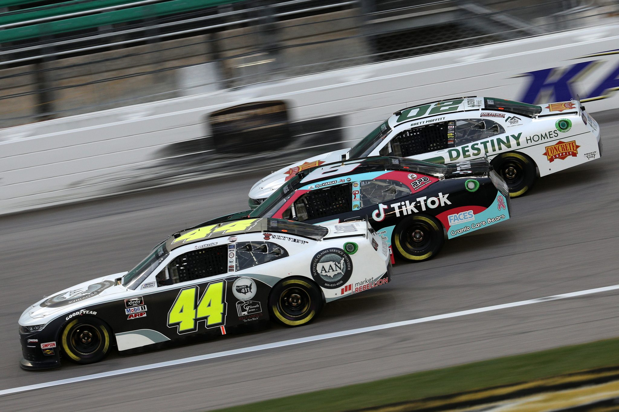 KANSAS CITY, KANSAS - OCTOBER 17: Tommy Joe Martins, driver of the #44 AAN Adjusters Chevrolet, Ryan Vargas, driver of the #6 TikTok Chevrolet, and Brett Moffitt, driver of the #02 Destiny Homes/Concrete Supply Chevrolet, race during the NASCAR Xfinity Series Kansas Lottery 300 at Kansas Speedway on October 17, 2020 in Kansas City, Kansas. (Photo by Chris Graythen/Getty Images) | Getty Images