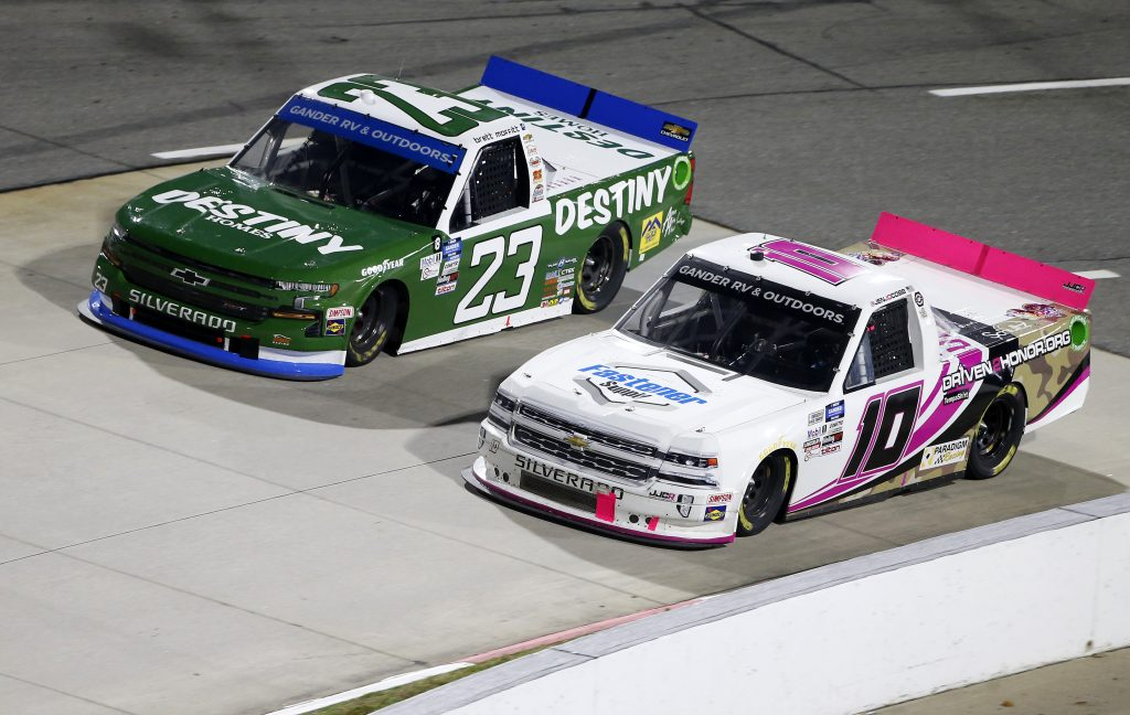 MARTINSVILLE, VIRGINIA - OCTOBER 30: Brett Moffitt, driver of the #23 Destiny Homes Chevrolet, and Jennifer Jo Cobb, driver of the #10 Fastener Supply Company Chevrolet, race during the NASCAR Gander RV & Outdoors Truck Series NASCAR Hall of Fame 200 at Martinsville Speedway on October 30, 2020 in Martinsville, Virginia. (Photo by Brian Lawdermilk/Getty Images)   Getty Images