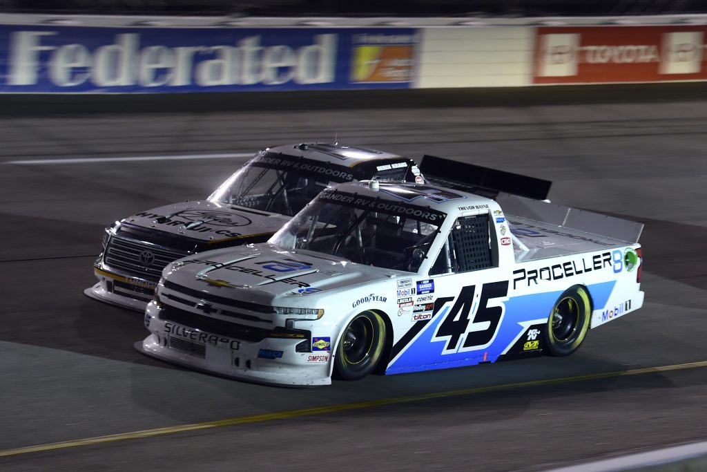 RICHMOND, VIRGINIA - SEPTEMBER 10: Trevor Bayne, driver of the #45 Plan B Sales/Proceller8 Chevrolet, and Derek Kraus, driver of the #19 Gates Hydraulics/NAPA Belts & Hoses Toyota, race during the NASCAR Gander Outdoors Truck Series ToyotaCare 250 at Richmond Raceway on September 10, 2020 in Richmond, Virginia. (Photo by Jared C. Tilton/Getty Images) | Getty Images