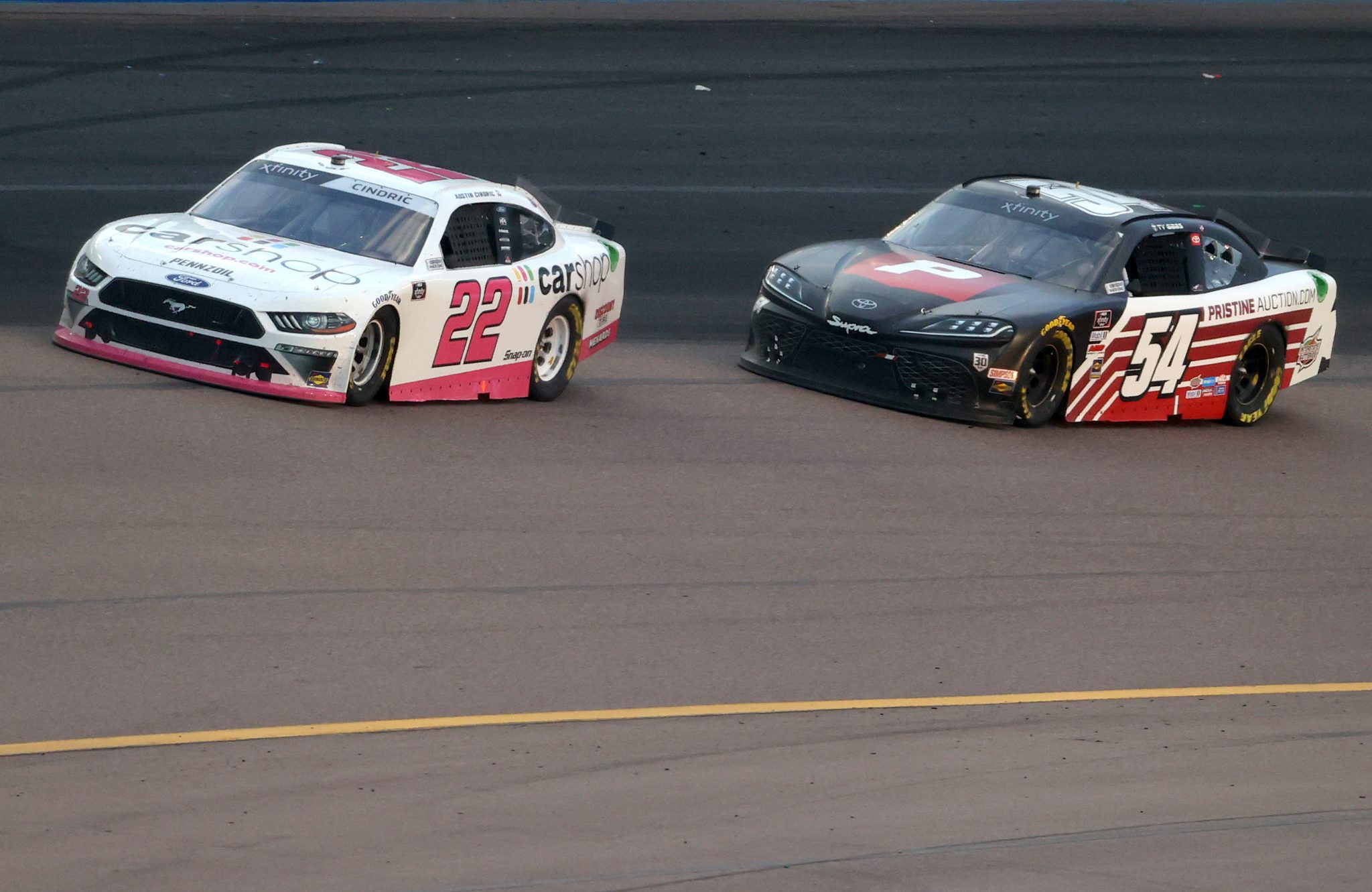 AVONDALE, ARIZONA - MARCH 13: Austin Cindric, driver of the #22 Car Shop Ford, and Ty Gibbs, driver of the #54 PristineAuction.com Toyota, race during the NASCAR Xfinity Series Call 811 Before You Dig 200 presented by Arizona 811 at Phoenix Raceway on March 13, 2021 in Avondale, Arizona. (Photo by Abbie Parr/Getty Images) | Getty Images