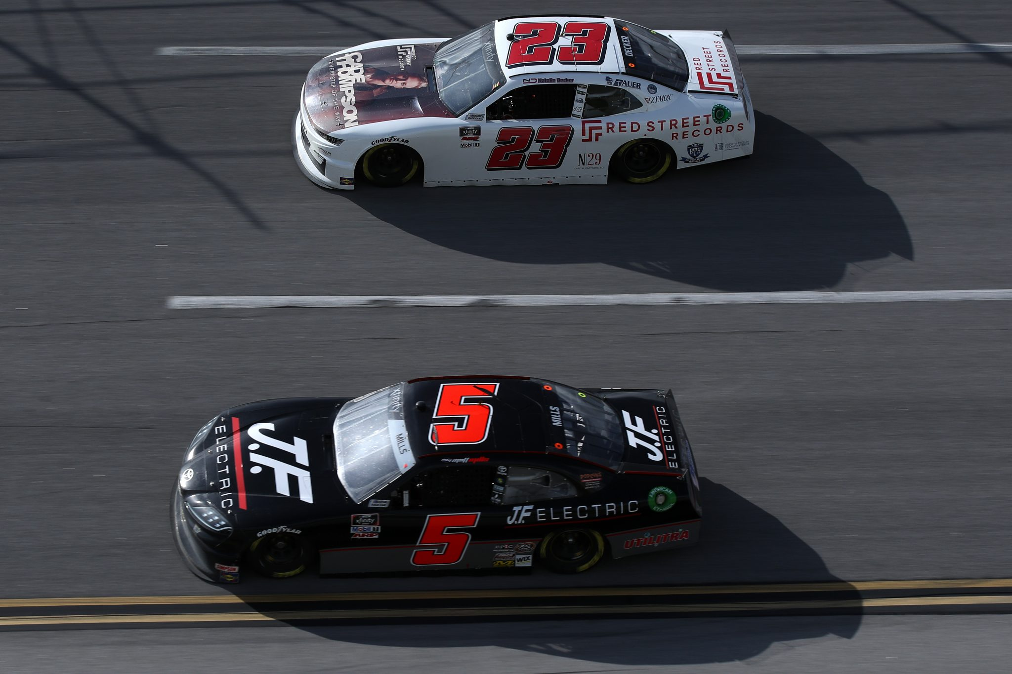 TALLADEGA, ALABAMA - APRIL 24: Matt Mills, driver of the #5 J.F. Electric Chevrolet, and Natalie Decker, driver of the #23 Red Street Records Chevrolet, race during the NASCAR Xfinity Series Ag-Pro 300 at Talladega Superspeedway on April 24, 2021 in Talladega, Alabama. (Photo by Sean Gardner/Getty Images) | Getty Images