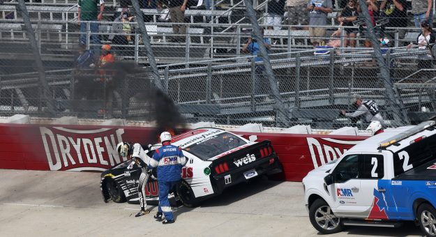 DOVER, DELAWARE - MAY 16: Aric Almirola, driver of the #10 Smithfield/Weis Markets Ford, exits his car as it catches fire after a wreck during the NASCAR Cup Series Drydene 400 at Dover International Speedway on May 16, 2021 in Dover, Delaware. (Photo by James Gilbert/Getty Images) | Getty Images