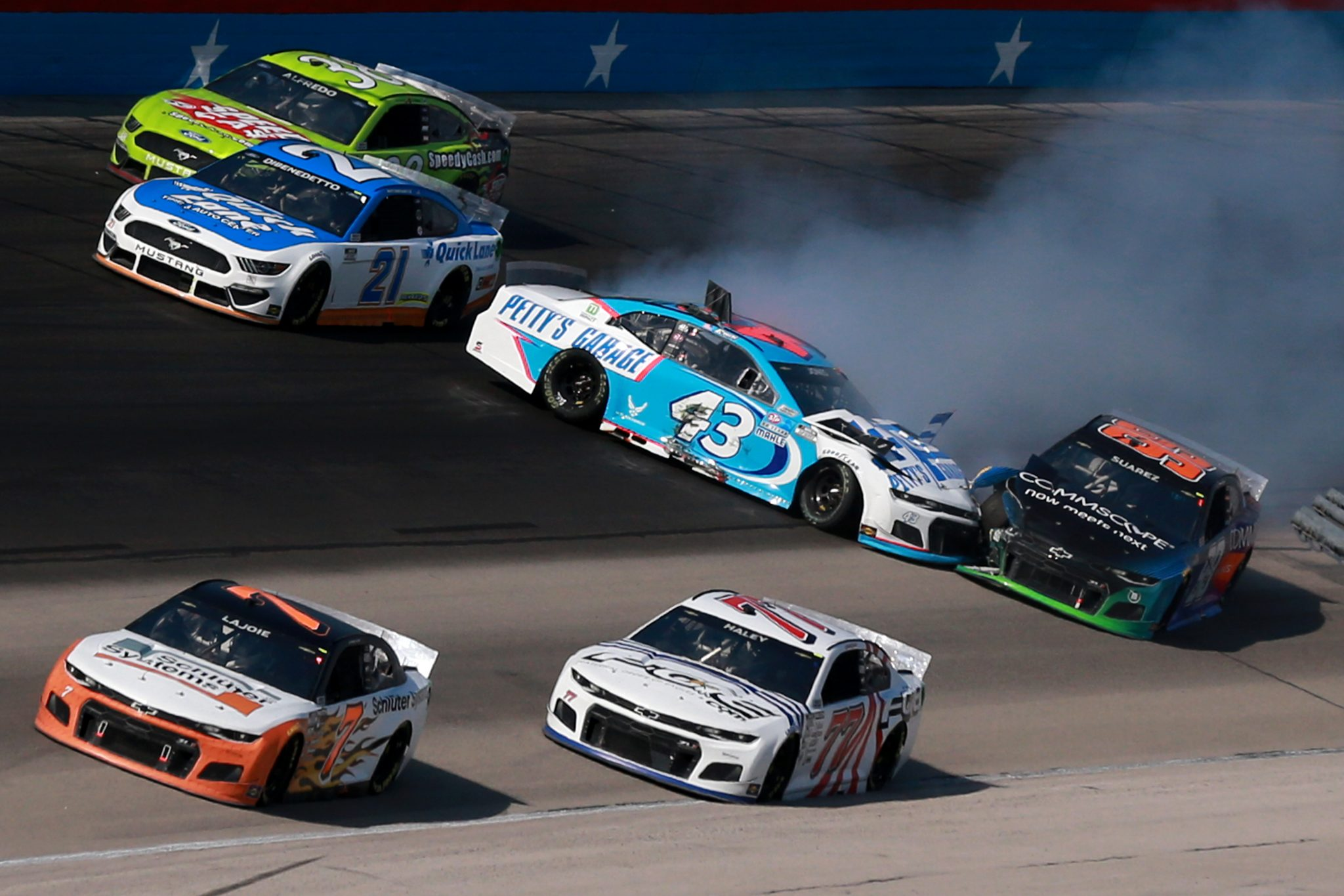 FORT WORTH, TEXAS - JUNE 13: Erik Jones, driver of the #43 Petty's Garage Chevrolet, spins into Daniel Suarez, driver of the #99 CommScope Chevrolet, as Corey LaJoie, driver of the #7 Schluter Systems Chevrolet, Justin Haley, driver of the #77 Fraternal Order of Eagles Chevrolet, and Matt DiBenedetto, driver of the #21 Quick Lane Tire & Auto Center Ford, avoid the on-track incident during the NASCAR All-Star Open at Texas Motor Speedway on June 13, 2021 in Fort Worth, Texas. (Photo by Sean Gardner/Getty Images) | Getty Images