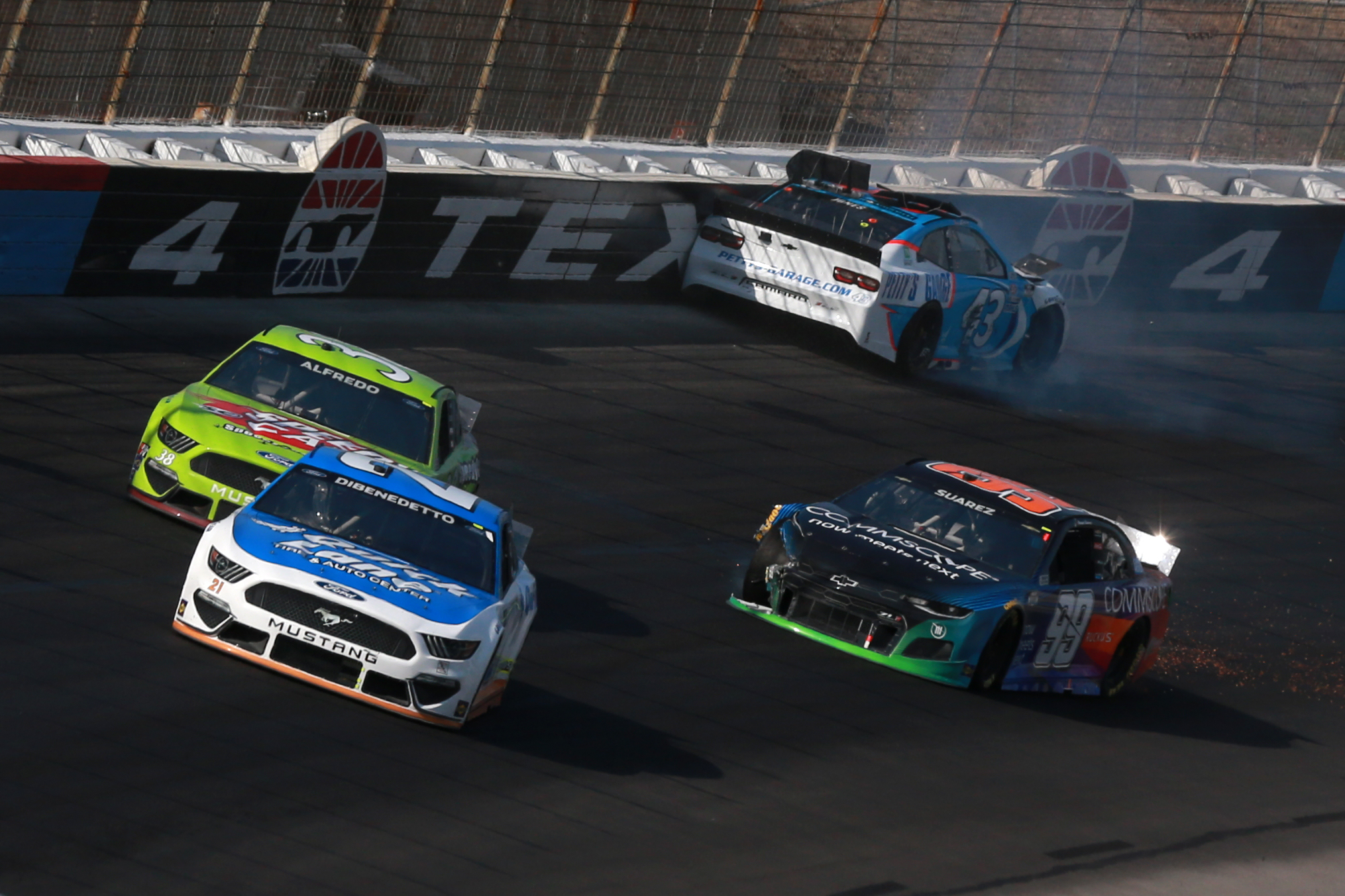 FORT WORTH, TEXAS - JUNE 13: Erik Jones, driver of the #43 Petty's Garage Chevrolet, spins into the wall as Matt DiBenedetto, driver of the #21 Quick Lane Tire & Auto Center Ford, Anthony Alfredo, driver of the #38 Speedy Cash Ford, and Daniel Suarez, driver of the #99 CommScope Chevrolet, drive past during the NASCAR All-Star Open at Texas Motor Speedway on June 13, 2021 in Fort Worth, Texas. (Photo by Sean Gardner/Getty Images)   Getty Images
