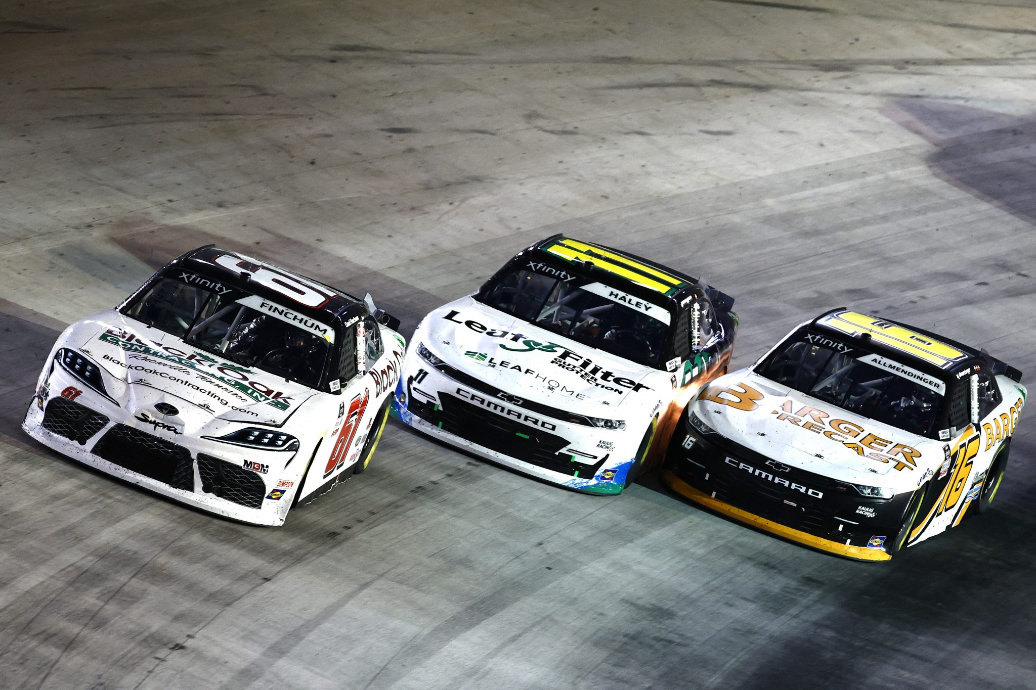 BRISTOL, TENNESSEE - SEPTEMBER 17: Chad Finchum, driver of the #61 Black Oak Contracting Toyota, Justin Haley, driver of the #11 LeafFilter Gutter Protection Chevrolet, and AJ Allmendinger, driver of the #16 Barger Precast Chevrolet, race during the NASCAR Xfinity Series Food City 300 at Bristol Motor Speedway on September 17, 2021 in Bristol, Tennessee. (Photo by Jared C. Tilton/Getty Images) | Getty Images
