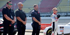BROOKLYN, MICHIGAN - AUGUST 21: Ty Gibbs, driver of the #54 SportClips Haircuts Toyota, and crew stand during the national anthem on the grid prior to the NASCAR Xfinity Series New Holland 250 at Michigan International Speedway on August 21, 2021 in Brooklyn, Michigan. (Photo by Logan Riely/Getty Images) | Getty Images